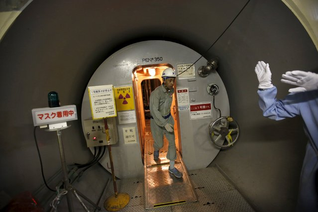 An employee of Kyushu Electric Power Co. walks through a gate of the reactor vessel inside the No. 1 reactor building where fuel rods are inserted into the reactor vessel at Sendai nuclear power station, in Satsumasendai, Kagoshima prefecture, Japan, July 8, 2015. (Photo by Issei Kato/Reuters)