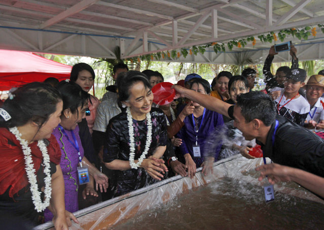 Myanmar's State Counsellor Aung San Suu Kyi, center, is doused with water by a man as she takes part in the last day of Myanmar traditional water festival, also known as Myanmar New Year, Sunday, April 16, 2017, in Naypyitaw, Myanmar. (Photo by Aung Shine Oo/AP Photo)