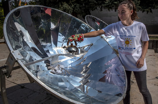 A High school student boils water for a tea on a solar furnace in the center of Negotino, Republic of North Macedonia, 19 September 2019. The event was organized by the NGO EKOVITA from Negotino with the purpose of educating young people about using renewable power sources and saving the environment. The solar furnaces were donated by the Swedish International Development Cooperation Agency. (Photo by Georgi Licovski/EPA/EFE)