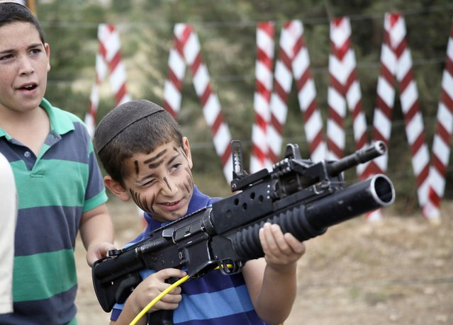 An Israeli boy plays with an M-16 rifle during a traditional military weapon display to mark the 66th anniversary of Israel's Independence at the West Bank settlement of Efrat on May 6, 2014 near the biblical city of Bethlehem. Israelis are marking Independence Day, celebrating the 66th year since the founding of the Jewish State in 1948 according to the Jewish calendar. (Photo by Gali Tibbon/AFP Photo)