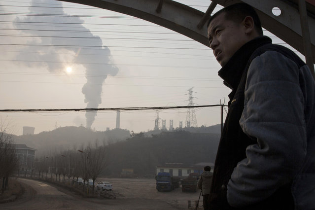 In this December 30, 2016 file photo, a man looks up near smoke spewing from a chimney near the Jiujiang steel and rolling mills in Qianan in northern China's Hebei province. Researchers say Tuesday, April 25, 2017 that China's conversion of coal into natural gas could prevent tens of thousands of premature deaths annually. But there's a catch: It also could undermine efforts to rein in greenhouse gas emissions. (Photo by Ng Han Guan/AP Photo)