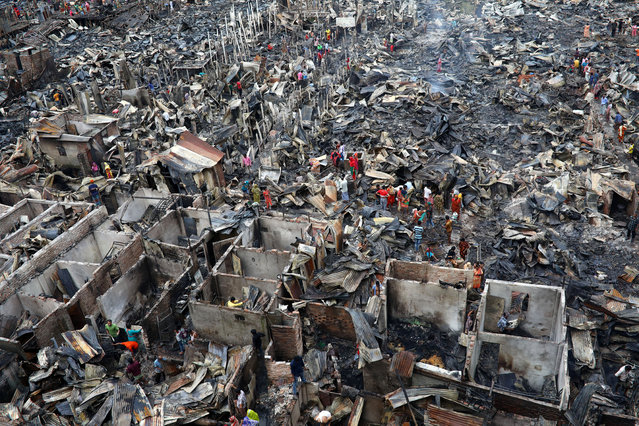 Slum dwellers are seen searching for their belongings from ashes after fire broke out on their shelters in Dhaka, Bangladesh, August 17, 2019. (Photo by Mohammad Ponir Hossain/Reuters)