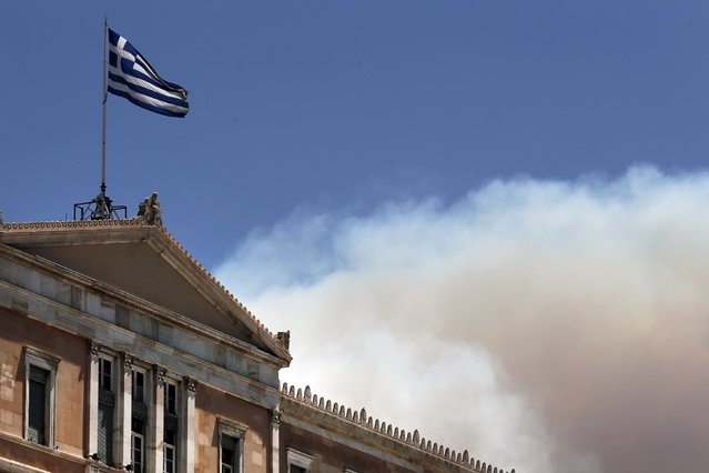 A Greek national flag flutters atop the parliament building as smoke from a raging wildfire rises in Athens, Greece July 17, 2015. (Photo by Alkis Konstantinidis/Reuters)