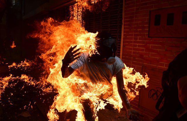 A demonstrator catches fire during clashes with riot police within a protest against Venezuelan President Nicolas Maduro, in Caracas on May 3, 2017. Venezuela' s angry opposition rallied Wednesday vowing huge street protests against President Nicolas Maduro' s plan to rewrite the constitution and accusing him of dodging elections to cling to power despite deadly unrest. (Photo by Ronaldo Schemidt/AFP Photo)