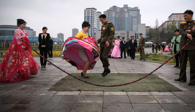 A bride and groom jump over a skipping rope as they pose during a wedding photo shoot at a park in Pyongyang on April 18, 2019. (Photo by Ed Jones/AFP Photo)