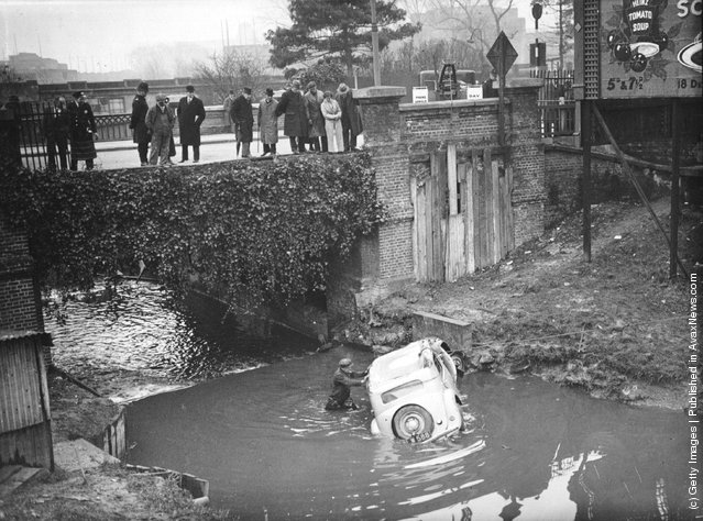 1936: A group of passers-by looking at a car which crashed through a fence and fell 20 feet into Wealdstone Brook, London