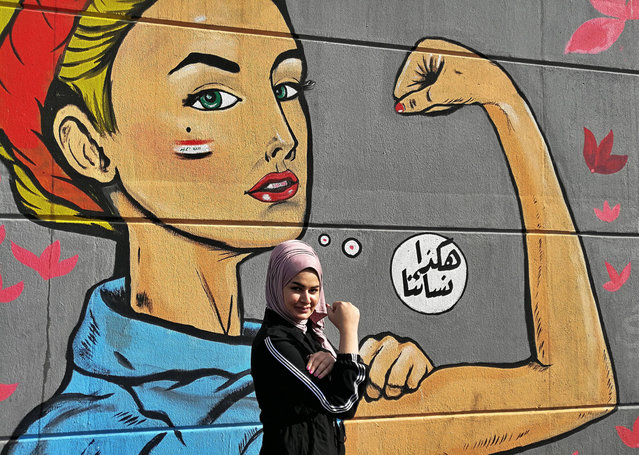 """A woman poses for a picture near a graffiti with Arabic reading """"those are our women"""" during ongoing protests near Tahrir Square in Baghdad, Iraq, Thursday, November 7, 2019. (Photo by Khalid Mohammed/AP Photo)"""