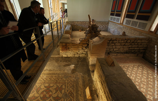 National Trust's Chedworth Roman Villa cleans a Roman mosiac in the new environmentally-controlled conservation shelter near Cirencester, England