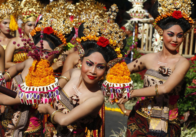 Indonesian dancers in traditional outfit perform during a parade to mark the Bali Arts Festival in Bali, Indonesia, Friday, June 13, 2014. Performances are scheduled daily during a month-long annual festival held from June 13 to July 12. (Photo by Firdia Lisnawati/AP Photo)