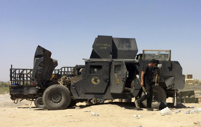 Iraqi counterterrorism forces fix their armored vehicles and load their weapons during a break in fighting outside Fallujah, Iraq, Tuesday, May 31, 2016. The elite troops repelled a four-hour attack by the Islamic State group in the city's south a day after first moving into the southern edges of the militant-held city with the help of U.S.-led coalition airstrikes. (Photo by Khalid Mohammed/AP Photo)