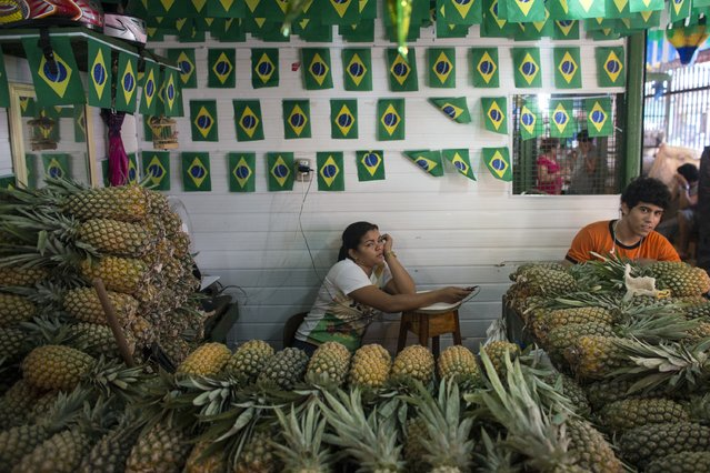 A market trader, adjacent to the port in Manaus, relaxes under decorations bearing the Brazilian national flag on June 14, 2014 in Manaus, Brazil. Group D teams, England and Italy, will play their opening match of the 2014 FIFA World Cup when they meet in Manaus this evening. (Photo by Oli Scarff/Getty Images)