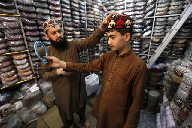 A Pakistani tries on a new prayer cap, ahead of the month of Ramadan, in Peshawar, Pakistan, 04 June 2016. Muslims around the world celebrate the holy month of Ramadan by praying during the night time and abstaining from eating and drinking during the period between sunrise and sunset. Ramadan is the ninth month in the Islamic calendar and it is believed that the Koran's first verse was revealed during its last 10 nights. (Photo by Bilawal Arbab/EPA)