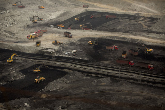 In this Wednesday, November 4, 2015, photo, vehicles work at an open-pit coal mine near Ordos in northern China's Inner Mongolia Autonomous Region. (Photo by Mark Schiefelbein/AP Photo)