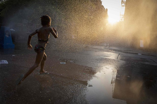 A young girl runs through a sprinkler at a playground in the Brooklyn borough of New York July 7, 2014. (Photo by Brendan McDermid/Reuters)