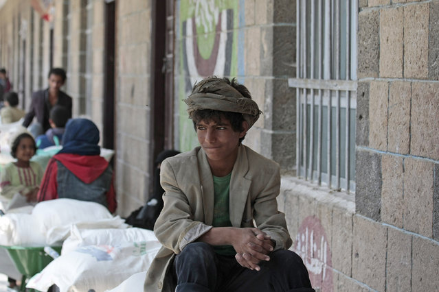 A boy waits for food supplies provided by the World Food Programme at a school in Sanaa, Yemen, Sunday, August 25, 2019. The U.N. humanitarian chief in Yemen warned last Wednesday that unless significant new funding is received in the coming weeks, food rations for 12 million people in the war-torn country will be reduced and at least 2.5 million malnourished children will be cut off from life-saving services. (Photo by Hani Mohammed/AP Photo)