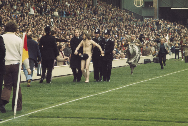 A streaker at Twickenham is discretely led off by police during the England v Wales rugby international, in London, England, 1974. (Photo by David Cannon/Allsport)