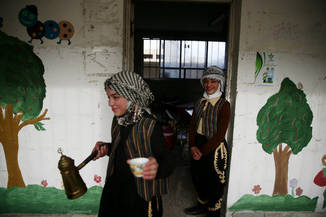 Girls wearing traditional men's clothing serve coffee during a celebration marking the end of the school year in the town of Douma, eastern Ghouta in Damascus, Syria May 21, 2016. (Photo by Bassam Khabieh/Reuters)