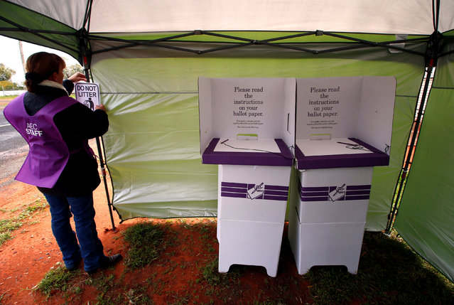 "Official Heather McInerney hangs a ""No Litter"" sign next to voting stands as she prepares a remote voting station in the western New South Wales outback town of Enngonia, Australia, June 22, 2016. (Photo by David Gray/Reuters)"