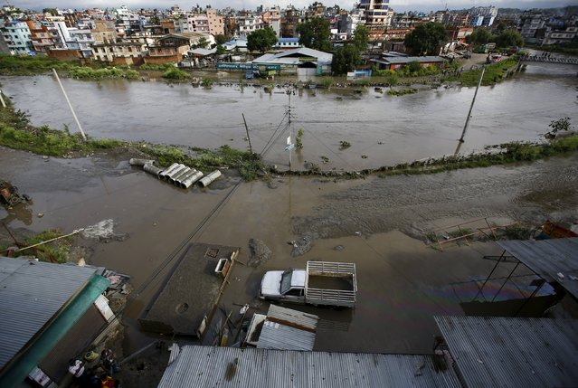 Floodwaters caused by heavy rainfall are seen among houses and slums along the swollen Bagmati River in Kathmandu, Nepal August 17, 2015. (Photo by Navesh Chitrakar/Reuters)