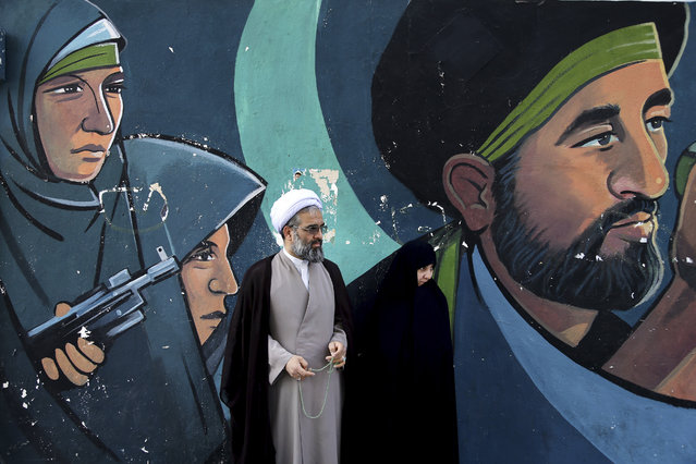 "A cleric and his wife stand in front of a mural showing depicting members of paramilitary Basij during an annual pro-Palestinian rally marking Al-Quds (Jerusalem) Day in Tehran, Iran, Friday, June 23, 2017. Iran held rallies across the country, with protesters condemning Israel's occupation of Palestinian territories and chanting ""Death to Israel"". (Photo by Ebrahim Noroozi/AP Photo)"