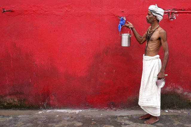 A Sadhu or a Hindu holyman fills water in a container before registering for the annual pilgrimage to the Amarnath cave shrine, at a base camp in Jammu, June 30, 2016. (Photo by Mukesh Gupta/Reuters)