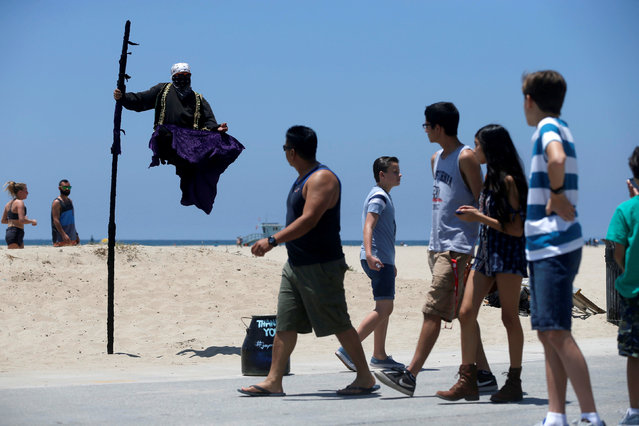 People watch a street performer in the Venice neighborhood of Los Angeles, California U.S., July 6, 2016. (Photo by Mario Anzuoni/Reuters)
