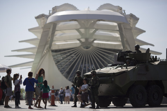 People take pictures with marines and their armored vehicle outside the Museum of Tomorrow in Rio de Janeiro, Brazil, Saturday, July 9, 2016. (Photo by Leo Correa/AP Photo)