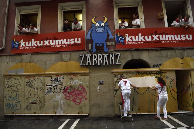 People protect a shop with floorboard in the Estafeta street before the beginning the fourth running of the bulls at the San Fermin Festival, in Pamplona, northern Spain, Sunday, July 10, 2016. (Photo by Alvaro Barrientos/AP Photo)