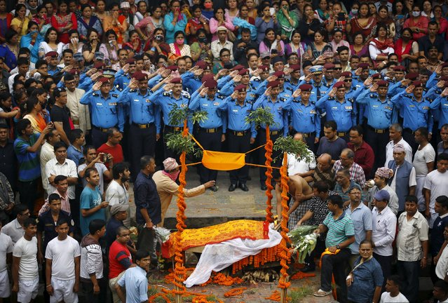 Nepali police officers salute as people watch the son (R) of Senior Superintendent of Police (SSP) Laxman Neupane cremate his father, who was killed in Monday's protest at Tikapur in Kailali district, in Kathmandu, Nepal August 25, 2015. Soldiers patrolled the small border town in Nepal's far west on Tuesday after nine people, most of them police, were killed in attacks by protesters angered by government reforms. (Photo by Navesh Chitrakar/Reuters)