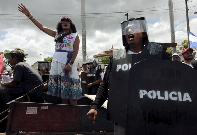 An opposition supporter dressed as Nicaragua's first lady Rosario Murillo waves during a protest to demand what the demonstrators said should be fairer presidential elections next year, in front of the Supreme Electoral Council (CSE) building in Managua, Nicaragua, August 26, 2015. (Photo by Oswaldo Rivas/Reuters)
