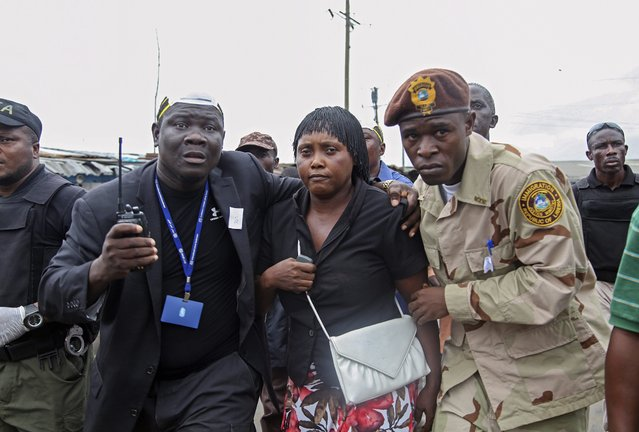 The Liberian commissioner of West Point, Miatta Flowers (C) is evacuated by community leaders and security forces after he home was beseiged by angry protestors in West Point, Monrovia, Liberia, 20 August 2014. (Photo by Ahmed Jallanzo/EPA)