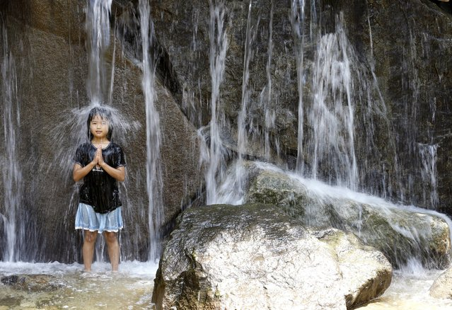 A girl stands under a water fall like a meditating Buddhist monk as she plays in the water fountain at Asuka Park in Tokyo, Monday, July 18, 2016. The temperature rose to 33 degrees Celsius (91 degrees Fahrenheit) in the Tokyo area. (Photo by Shizuo Kambayashi/AP Photo)