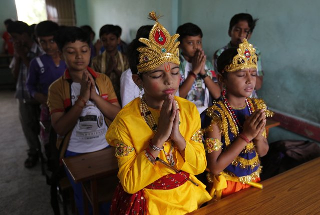 Students dressed as Hindu Lord Krishna (C) and his consort Radha (R) offer school prayers inside their classroom during celebrations marking the Janmashtami festival in the western Indian city of Ahmedabad August 16, 2014. The festival, which marks the birth anniversary of Lord Krishna, will be celebrated across India on Monday. (Photo by Amit Dave/Reuters)
