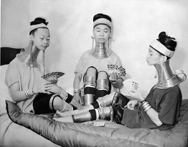 Three Burmese women members of a circus play cards as they wear the brass neck and leg rings traditionally worn by Padaung women since childhood and which cannot be removed, London, January 4, 1935. (Photo by Keystone)