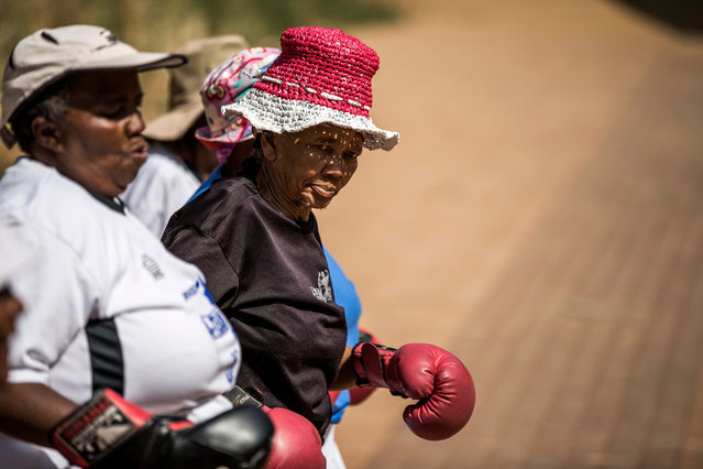 "77 year-old Gladys Ngwenya (C) leads others as they walk after taking part in a ""Boxing Gogos"" (Grannies) training session hosted by the A Team Gym in Cosmo City in Johannesburg on September 19, 2017. (Photo by Gulshan Khan/AFP Photo)"