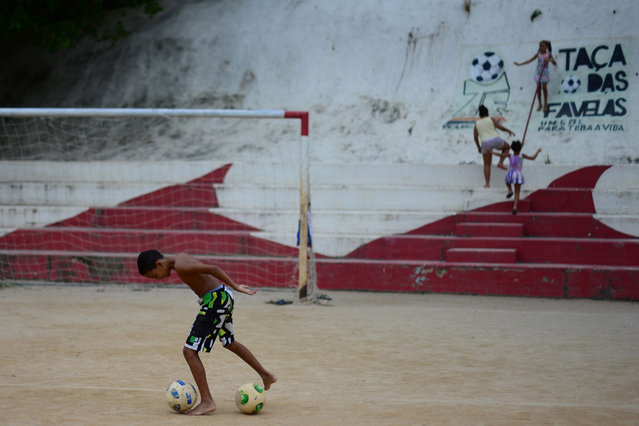 Christophe Simon, AFP chief photographer in Brazil, gathered together a group of 18 teen- agers in Cidade de Deus favela in Rio de Janeiro, and, working together, they photographed their everyday life featuring their love of football, and at a time before every camera in the world was focused on Brazil and the 2014 Football World Cup. (Photo by Christophe Simon/AFP Photo)
