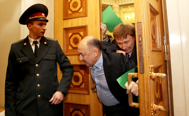 Ukrainian deputies push and shove on December 12, 2012 members of Parliament Alexander Tabalov (C) and his son Andrey before the opening ceremony of the newly elected Ukrainian parliament in Kiev. (Photo by AFP Photo/Stringer)