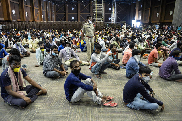 Stranded migrant workers sit in a waiting hall before registering with police officials for a movement pass to be able to return to their hometowns after the government eased a nationwide lockdown imposed as a preventive measure against the COVID-19 coronavirus, on the outskirts of Hyderabad on May 5, 2020. (Photo by Noah Seelam/AFP Photo)