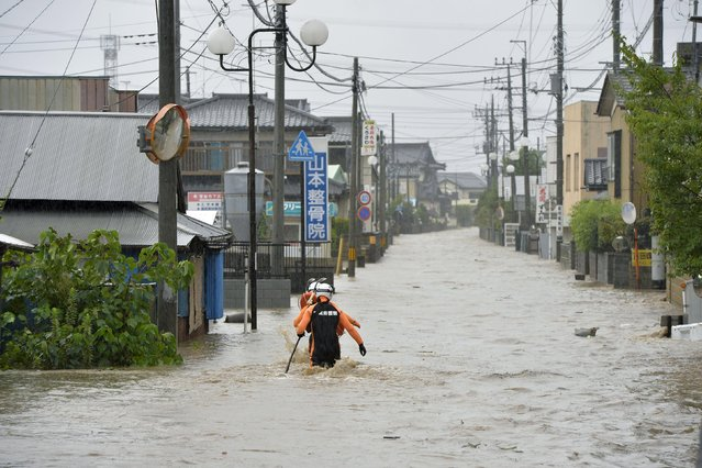 Police officers wade through a residential area flooded by the Kinugawa river, caused by typhoon Etau in Joso, Ibaraki prefecture, Japan, in this photo taken by Kyodo September 10, 2015. (Photo by Reuters/Kyodo News)