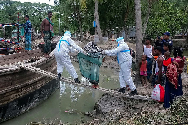 "This handout photo taken on May 19, 2020 and released by the District Administration of Bhola shows residents being evacuted in Dhalchar village on the island of Bhola as Cyclone Amphan barrels towards Bangladesh's coast. Millions of people were being moved to safety as one of the fiercest cyclones in years barrelled towards India and Bangladesh on May 19, but with evacuation plans complicated by coronavirus precautions. ""Amphan"" is expected to pack winds gusting up to 185 kilometres (115 miles) per hour when it hits eastern India and Bangladesh on May 20 afternoon or evening, and with a storm surge of several metres, forecasters said. (Photo by District Administration of Bhola/AFP Photo)"