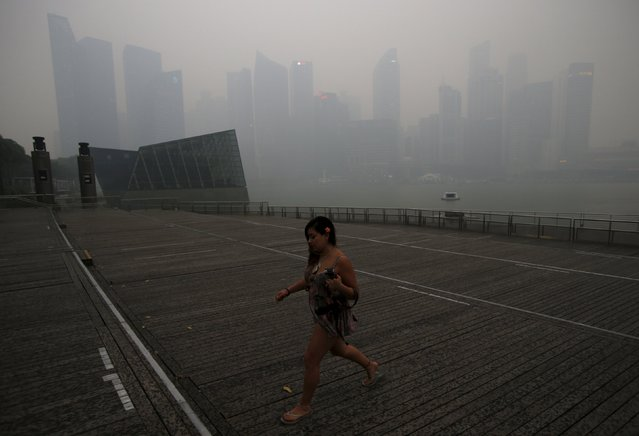 A woman passes the skyline of the central business district shrouded by haze in Singapore September 14, 2015. (Photo by Edgar Su/Reuters)