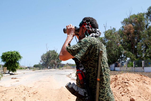 A fighter of Libyan forces allied with the U.N.-backed government looks through a pair of binoculars during a battle with Islamic State fighters in Sirte, Libya August 15, 2016. (Photo by Ismail Zitouny/Reuters)