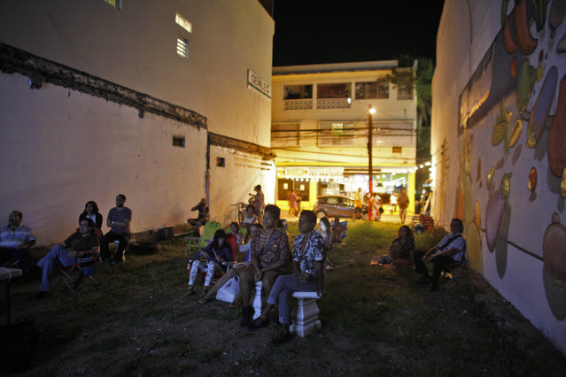 In this September 21, 2014 photo, people watch a movie at a makeshift outdoor movie theater in the Santurce neighborhood in San Juan, Puerto Rico. (Photo by Ricardo Arduengo/AP Photo)