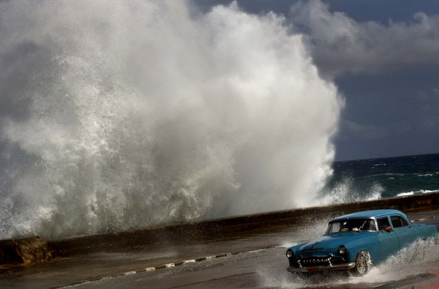 A driver maneuvers his classic American car along a wet road as a wave crashes against the Malecon in Havana, Cuba on Thursday. Hurricane Sandy blasted across eastern Cuba as a potent Category 2 storm and headed for the Bahamas after causing at least two deaths in the Caribbean. (Photo by Ramon Espinosa/Associated Press)