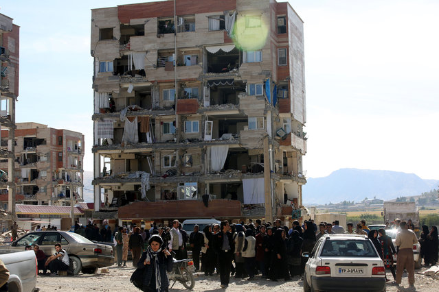 Earthquake survivors mourn for the victims in Sarpol-e Zahab town of Kermanshah, Iran on November 13, 2017 following a 7.3 magnitude earthquake that hit the Iraq and Iran. An earthquake measuring 7.3 on the Richter scale rocked northern Iraq and Iran, the U.S. Geological Survey said on Sunday evening. Turkish paramedic teams and rescue teams dispatched to the disaster area under the coordination of Turkish aid agencies; AFAD (Turkey's Disaster Management Agency) and Kizilay (Turkish Red Crescent). At least 211 died and 2,504 others were injured in Iran's bordering regions, especially in Kermanshah province in west. (Photo by Fatemeh Bahrami/Anadolu Agency/Getty Images)