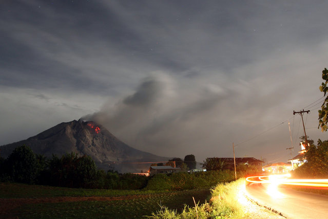 Mount Sinabung spews hot lava and volcanic ash as it is seen from Sibintun village, Karo, North Sumatra, Indonesia, October 10, 2014. Mount Sinabung has been erupting over the last five days, forcing hundreds of people to flee their homes. The 2,460-metre volcano had been dormant for 400 years before it erupted in August 2010. (Photo by Dedy Sahputra/EPA)