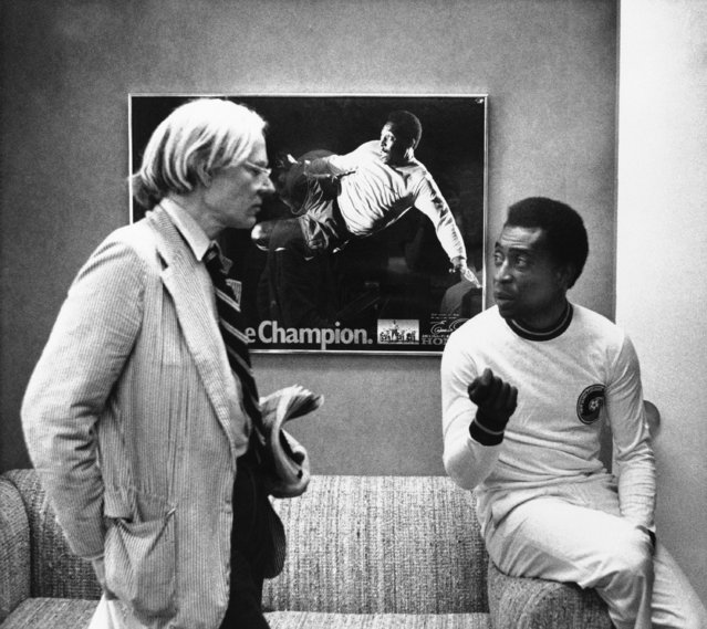 Pop artist Andy Warhol, left, and soccer superstar Pele discuss a portrait Warhol is making of Pele during a recent get-together on July 26, 1977 in New York. In background is a poster with a photograph of Pele in action. Warhol has been commissioned to make a series of portrait of athletic stars. (Photo by Claudia Larson/AP Photo)