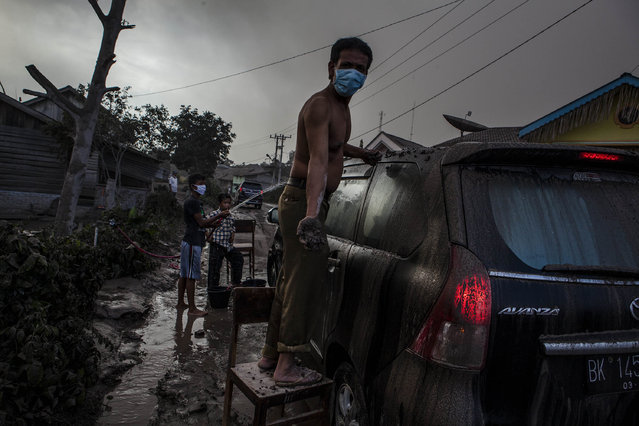 A man cleans his car as their village is hit by ash from the eruption of Mount Sinabung on October 13, 2014 in Berastagi, Karo district, North Sumatra, Indonesia. (Photo by Ulet Ifansasti/Getty Images)
