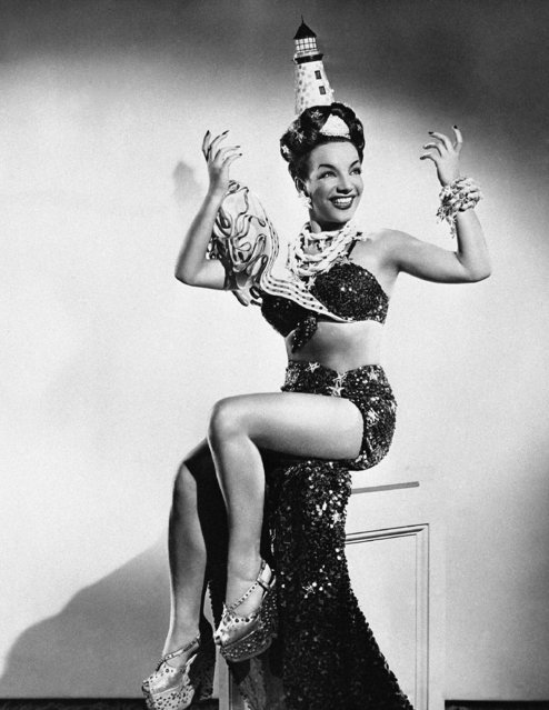 """Carmen Miranda tries new high hats thought up designers, such as this miniature lighthouse which she wears in the film """"Doll Face"""", on September 24, 1945. She does not appear to mind the weight of it either for it lights up from its own batteries. To increase her stature, Miranda wear jewel-studded thick sold platform shoes. (Photo by AP Photo)"""