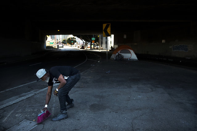 "Thurman Butler Jr., 66, who is homeless, sweeps around his tent Friday, December 1, 2017, in Los Angeles. ""A lot of people in America don't realize they might be two checks, three checks, four checks away from being homeless"", said Butler who became homeless after he was evicted from his apartment. A homeless crisis of unprecedented proportions is rocking the West Coast, and its victims are being left behind by the very things that mark the region's success: soaring housing costs, rock-bottom vacancy rates and a roaring economy that waits for no one. (Photo by Jae C. Hong/AP Photo)"